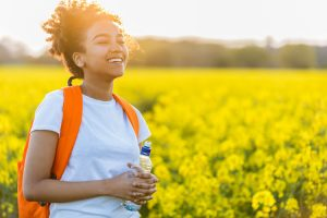Outdoor Portrait Of Beautiful Happy Laughing Mixed Race African American Girl Teenager Female Young Woman With Drinking Water Bottle In A Field Of Yel